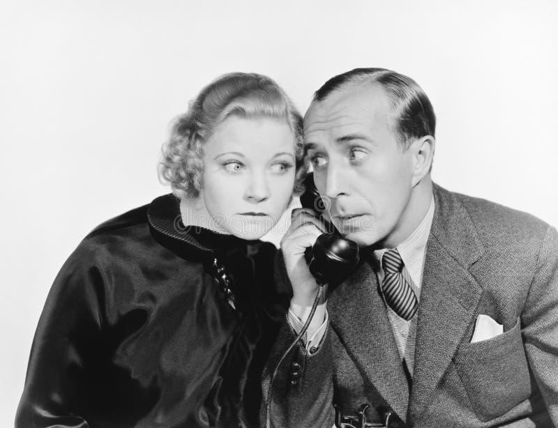 Άνδρας και μια γυναίκα που κρυφακούει στο τηλέφωνο (όλα τα πρόσωπα που απεικονίζονται δεν ζουν περισσότερο και κανένα κτήμα δεν υ στοκ εικόνες