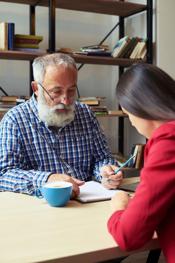 Άνδρας που γράφει στο σημειωματάριο και τη νέα γυναίκα στοκ φωτογραφίες