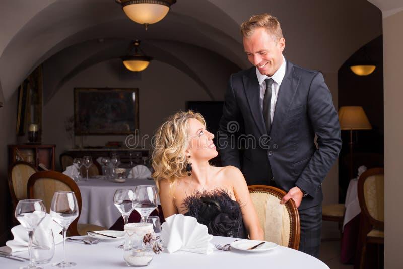 Άνδρας που είναι κύριος και που βοηθά τη γυναίκα με την καρέκλα της στοκ φωτογραφίες
