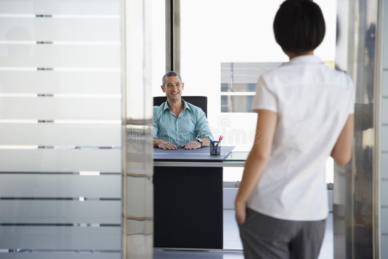 Άνδρας που μιλά στη στάση γυναικών στην πόρτα γραφείων στοκ εικόνες