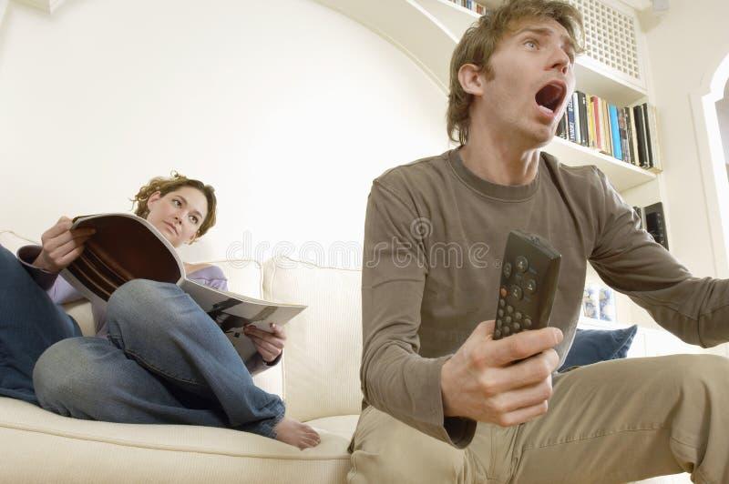 Άνδρας που προσέχει τη TV με το περιοδικό ανάγνωσης γυναικών στοκ φωτογραφία