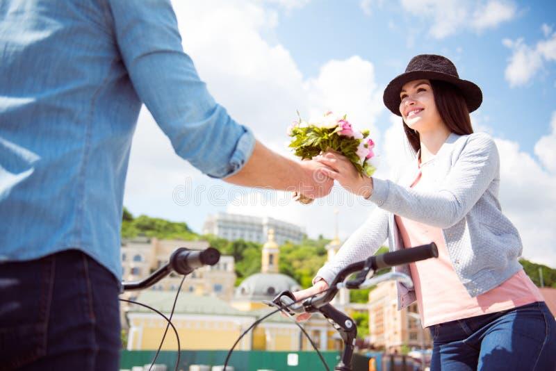 Άνδρας που προσφέρει τα λουλούδια στη γυναίκα στο καπέλο στοκ φωτογραφία