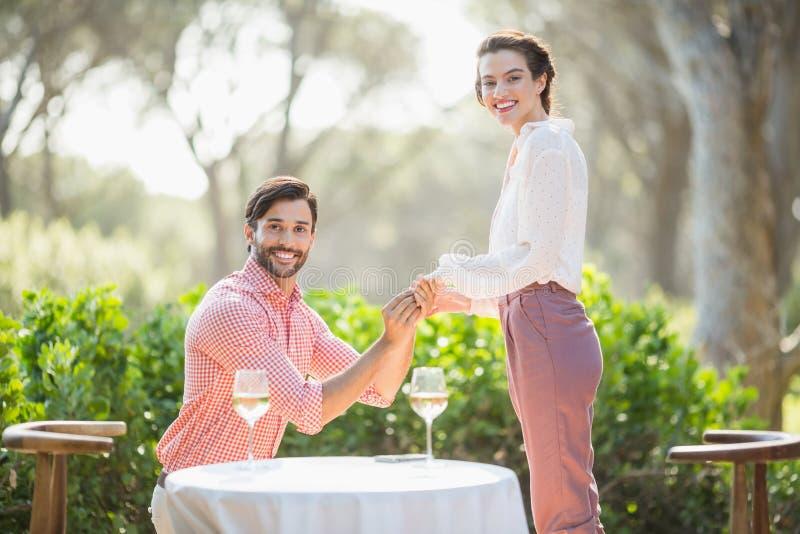 Άνδρας που προτείνει μια γυναίκα με ένα δαχτυλίδι στο γόνατό του στο εστιατόριο στοκ φωτογραφίες