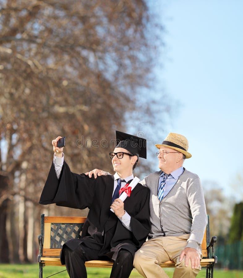 Άνδρας σπουδαστής και ο πατέρας του που παίρνουν selfie στο πάρκο στοκ φωτογραφία με δικαίωμα ελεύθερης χρήσης