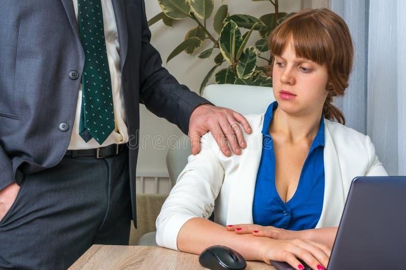 Άνδρας σχετικά με τον ώμο γυναικών ` s - σεξουαλική παρενόχληση στην αρχή στοκ φωτογραφίες