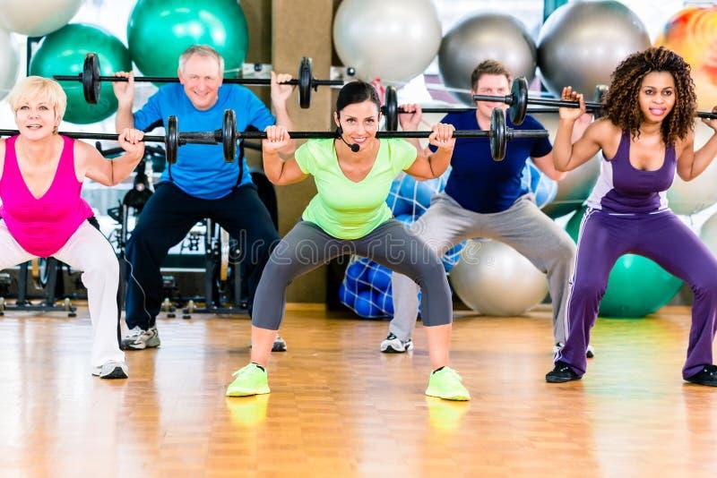 Άνδρες και γυναίκες που ανυψώνουν barbell στη γυμναστική στοκ εικόνα