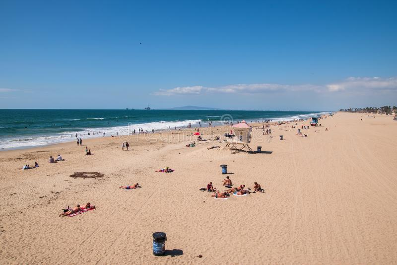 Άποψη άνωθεν η ευρεία αμμώδης παραλία του Χάντινγκτον Μπιτς Καλιφόρνια που παρουσιάζει τους κολυμβητές και surfers sunbathers στοκ εικόνες