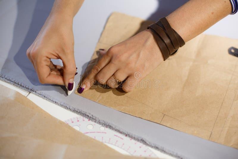 Άποψη άνωθεν σε διαθεσιμότητα seamstress με έναν κυβερνήτη Μετρά τη γραμμή περικοπών του υφάσματος στα κενά και σύρει το σαπούνι  στοκ εικόνα