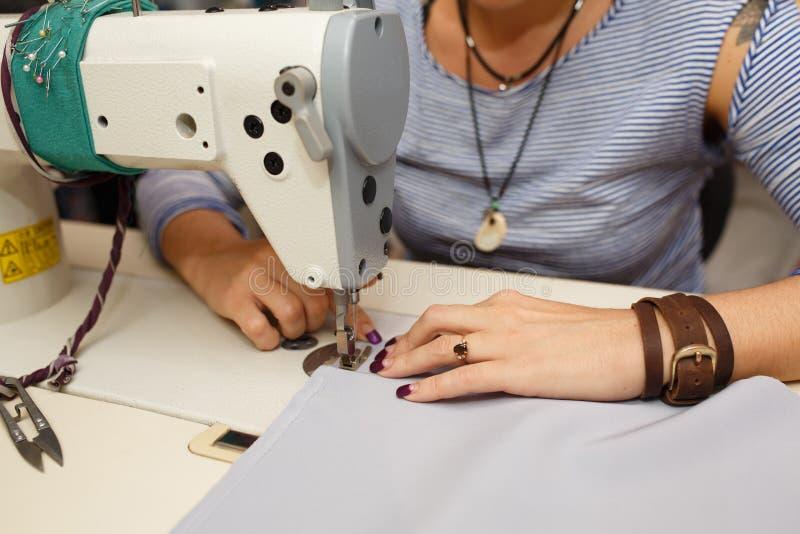 Άποψη άνωθεν σε ετοιμότητα του θηλυκού ράφτη που λειτουργούν στη ράβοντας μηχανή βιομηχανία κατασκευής φορεμάτων στοκ φωτογραφία με δικαίωμα ελεύθερης χρήσης