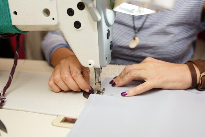 Άποψη άνωθεν σε ετοιμότητα του θηλυκού ράφτη που λειτουργούν στη ράβοντας μηχανή βιομηχανία κατασκευής φορεμάτων στοκ φωτογραφίες