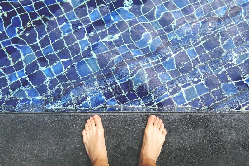 Άποψη άνωθεν σχετικά με τα γυμνά αρσενικά πόδια στην πλευρά πισινών στοκ εικόνα