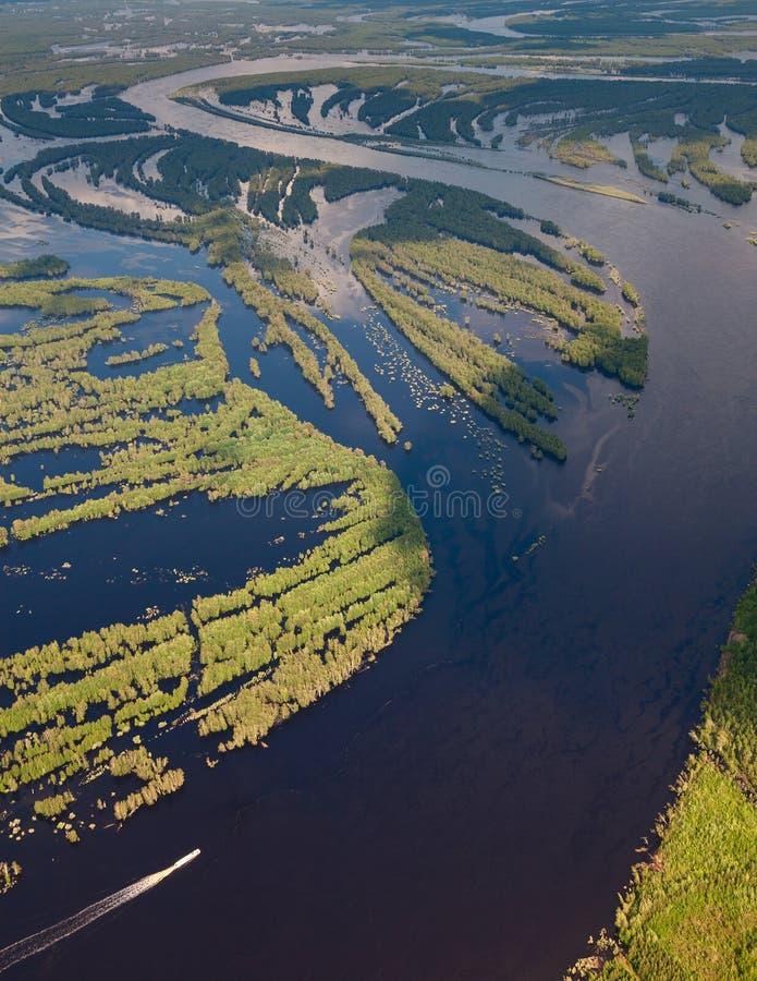 Άποψη άνωθεν του σκάφους αναψυχής στο δασικό ποταμό κατά τη διάρκεια της πλημμύρας στοκ εικόνα με δικαίωμα ελεύθερης χρήσης