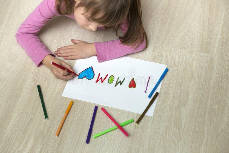 Άποψη άνωθεν του χαριτωμένου σχεδίου κοριτσιών παιδιών με τα ζωηρόχρωμα κραγιόνια Ι αγάπη Mom στη Λευκή Βίβλο Αισθητική αγωγή, έν στοκ φωτογραφία