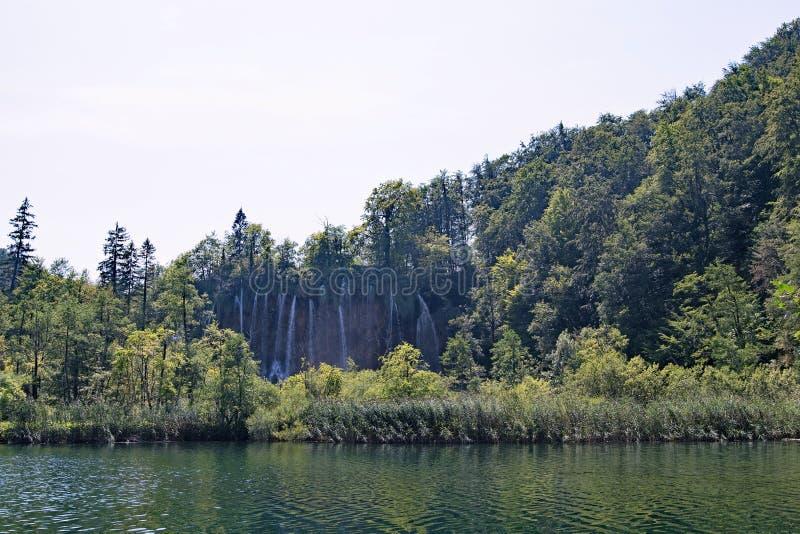 Άποψη απόστασης ενός μεγάλου καταρράκτη πίσω από τη θαμνώδη περιοχή, στο εθνικό πάρκο λιμνών Plitvice, στην Κροατία στοκ εικόνες