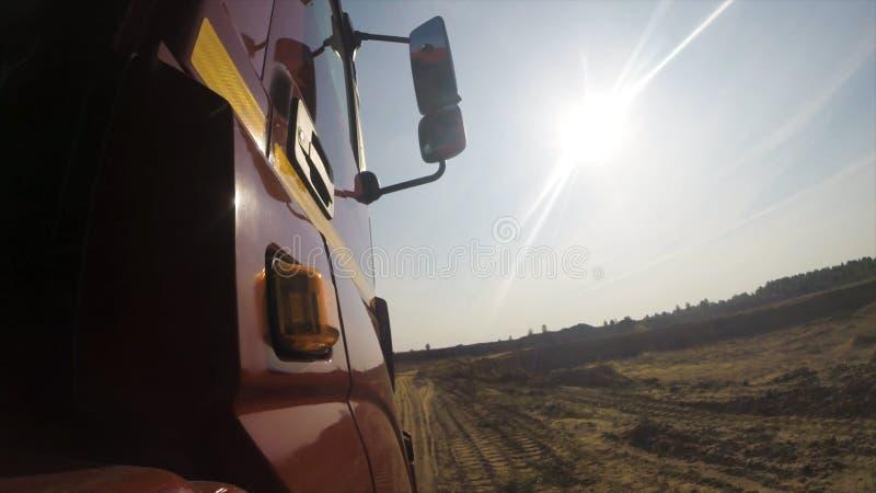 Άποψη από μια ρόδα του πλαϊνού φορτηγού που οδηγά σε έναν βρώμικο δρόμο στο νεφελώδες υπόβαθρο ουρανού σκηνή Κλείστε επάνω για το στοκ φωτογραφία με δικαίωμα ελεύθερης χρήσης