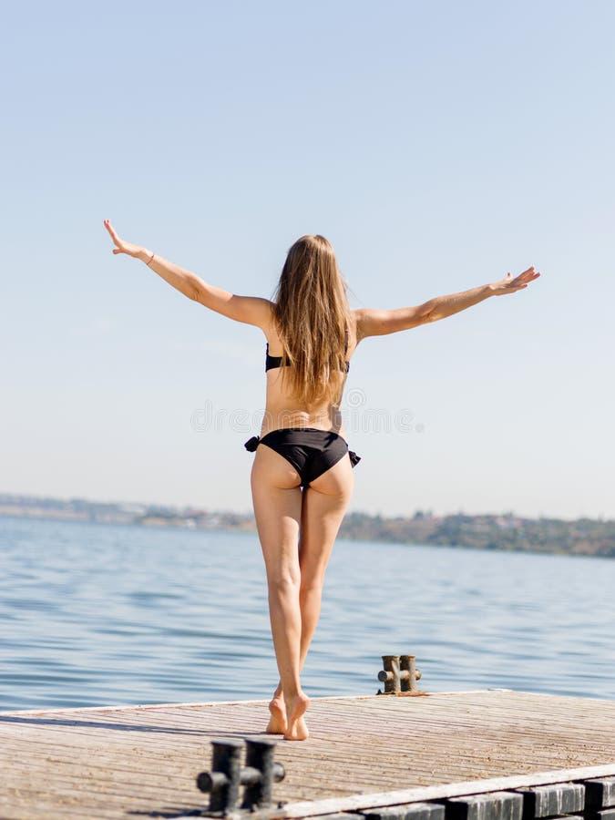 Άποψη από την πλάτη μιας λεπτής γυναίκας που περπατά σε μια αποβάθρα στο υπόβαθρο νερού υγιής τρόπος ζωής έννοιας στοκ εικόνα με δικαίωμα ελεύθερης χρήσης