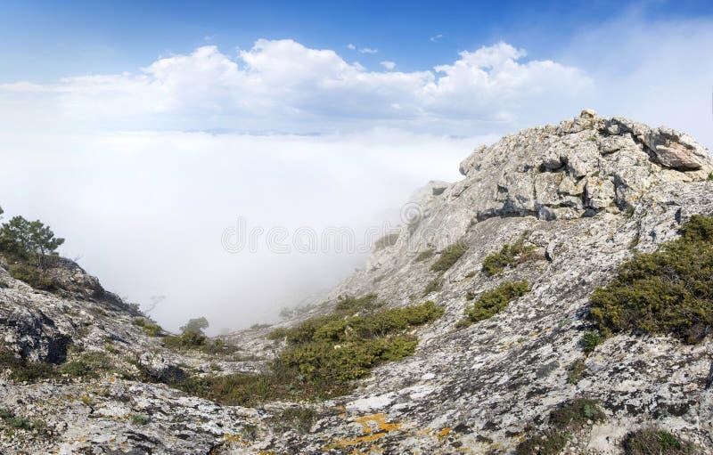 Άποψη από τη δύσκολη κορυφή του βουνού επάνω από τα σύννεφα στοκ εικόνα