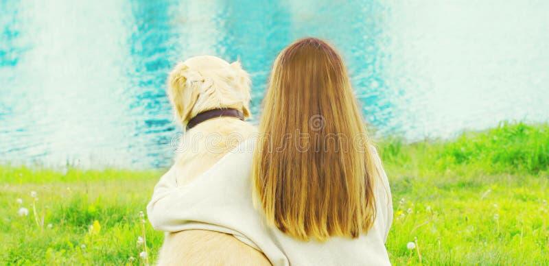 άποψη από τον πίσω ιδιοκτήτη με τη χρυσή Retriever συνεδρίαση σκυλιών μαζί στη χλόη κοντά στον ποταμό στοκ εικόνα