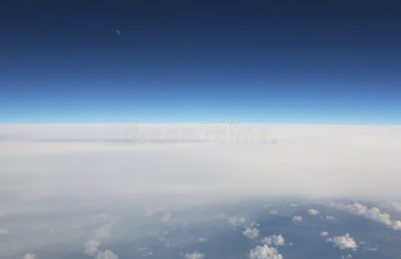 Άποψη από το παράθυρο αεροπλάνων, το μπλε ουρανό και τα άσπρα σύννεφα στοκ φωτογραφίες