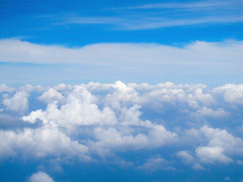 Άποψη από το παράθυρο των αεροσκαφών στα όμορφα σύννεφα και το φωτεινό μπλε ουρανό στοκ εικόνες