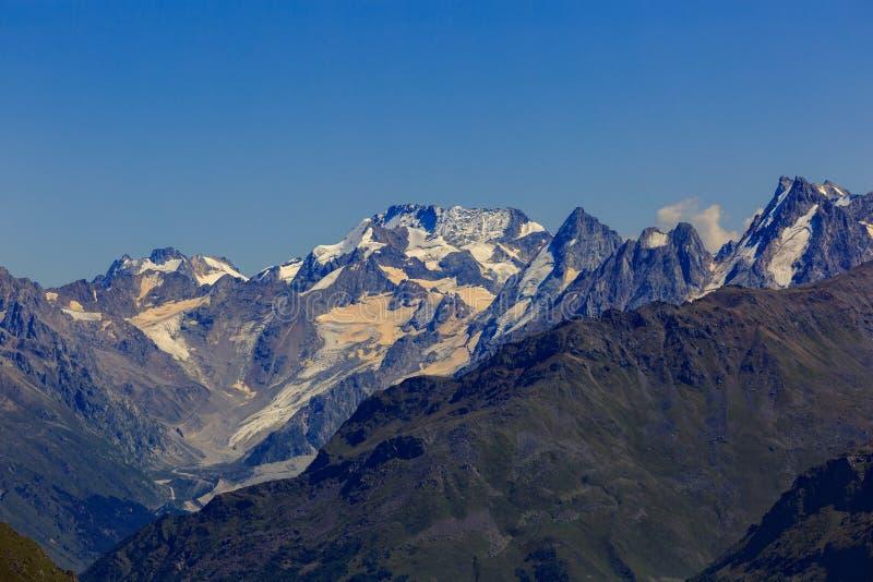 Άποψη από Elbrus στις περιβάλλουσες αιχμές βουνών με το χιόνι στοκ εικόνα