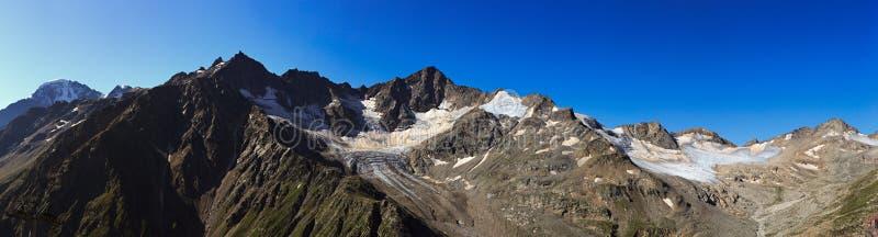 Άποψη από Elbrus στις περιβάλλουσες αιχμές βουνών με το χιόνι στοκ φωτογραφία με δικαίωμα ελεύθερης χρήσης