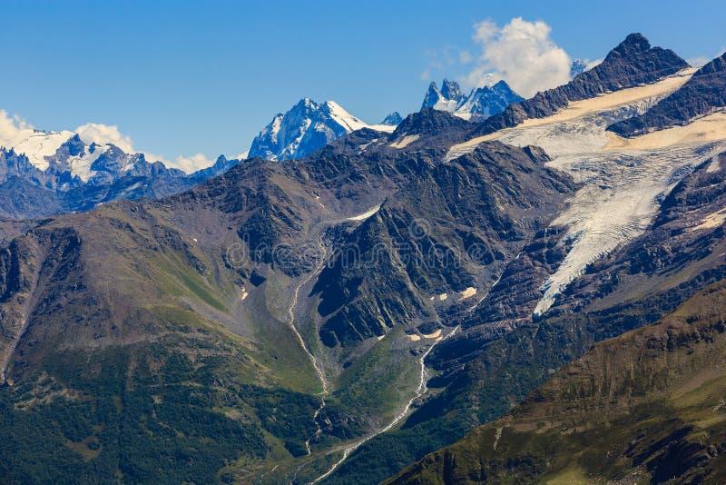 Άποψη από Elbrus στις περιβάλλουσες αιχμές βουνών με το χιόνι στοκ φωτογραφία