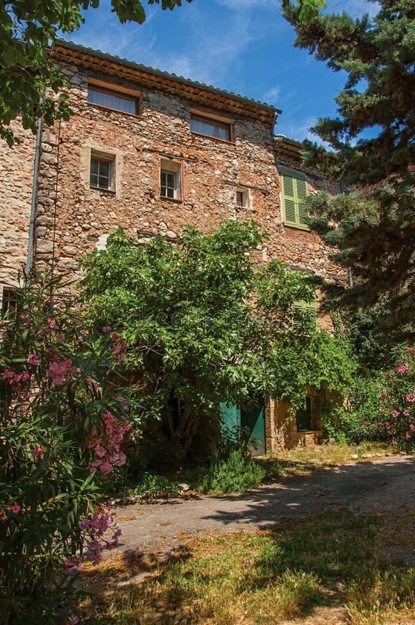 Άποψη αλεών με το σπίτι και τα λουλούδια σε Châteaudouble στοκ εικόνες