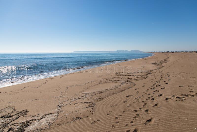 Άποψη γραμμών ακτών με τις τυπωμένες ύλες ποδιών στην άμμο στοκ εικόνες με δικαίωμα ελεύθερης χρήσης