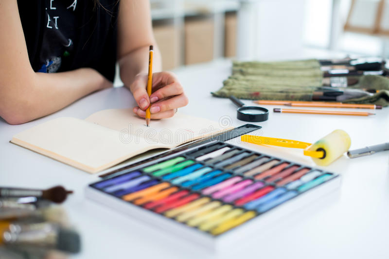 Άποψη γωνίας κινηματογραφήσεων σε πρώτο πλάνο ενός θηλυκού σχεδίου σχεδίων ζωγράφων στο sketchbook που χρησιμοποιεί το μολύβι Καλ στοκ εικόνες με δικαίωμα ελεύθερης χρήσης