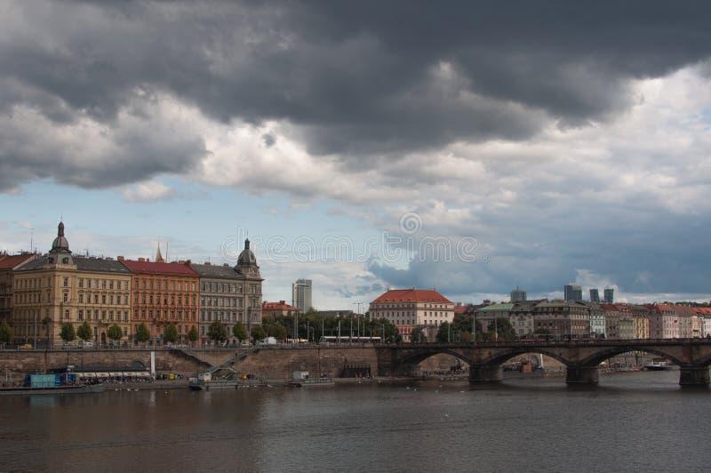 Άποψη εικονικής παράστασης πόλης σχετικά με την όχθη ποταμού με τη γέφυρα και την παλαιά πόλη στην Πράγα στοκ φωτογραφίες