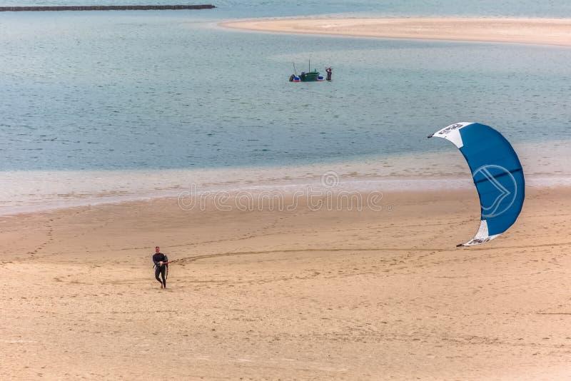 Άποψη ενός αρσενικού επαγγελματικού Kiteboarder που περπατά στην παραλία άμμου, στη λιμνοθάλασσα Obidos στοκ φωτογραφία με δικαίωμα ελεύθερης χρήσης