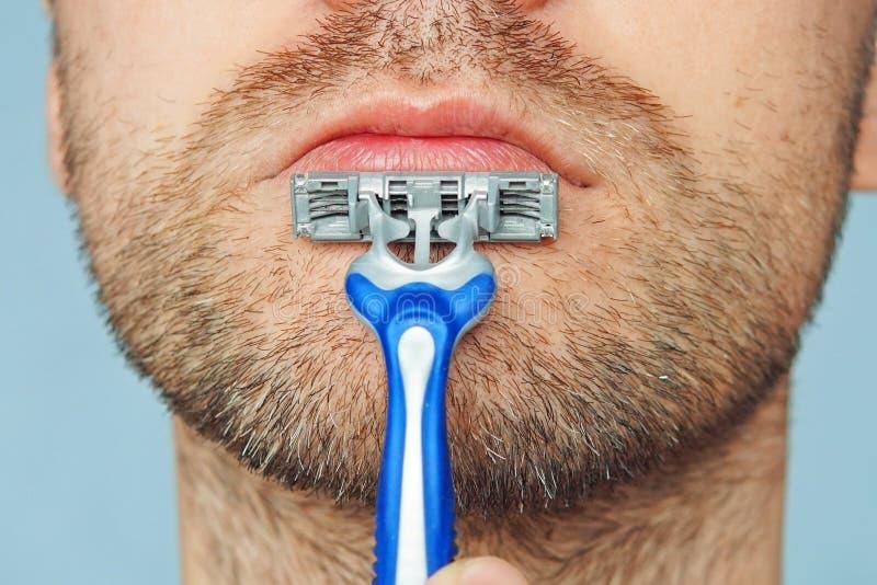 Άποψη ενός νέου γενειοφόρου ατόμου με ένα βάναυσο ξυράφι πρόσωπο στο μπλε υπόβαθρο οι μεγάλες τραχιές τριχωτές σκληρές τρίχες στο στοκ εικόνες με δικαίωμα ελεύθερης χρήσης