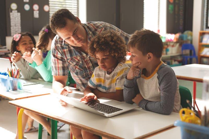 Άποψη επιπέδων επιφάνειας μιας διδασκαλίας δασκάλων πώς να χρησιμοποιήσει ένα lap-top στους μαθητές του στοκ εικόνα με δικαίωμα ελεύθερης χρήσης