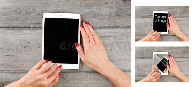 Άποψη επιτραπέζιων κορυφών σχετικά με τη νέα ταμπλέτα εκμετάλλευσης χεριών γυναικών, στο γκρίζο ξύλο στοκ εικόνα