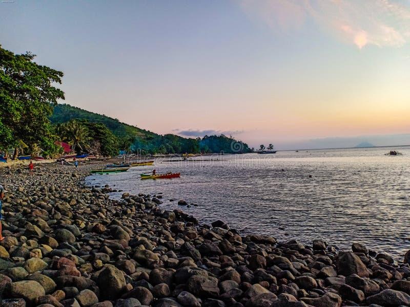 Άποψη ηλιοβασιλέματος σχετικά με την παραλία στο χωριό Aerbanua, νησί Talise, ο Βορράς Sulawesi, Ινδονησία ψαράδων στοκ φωτογραφίες