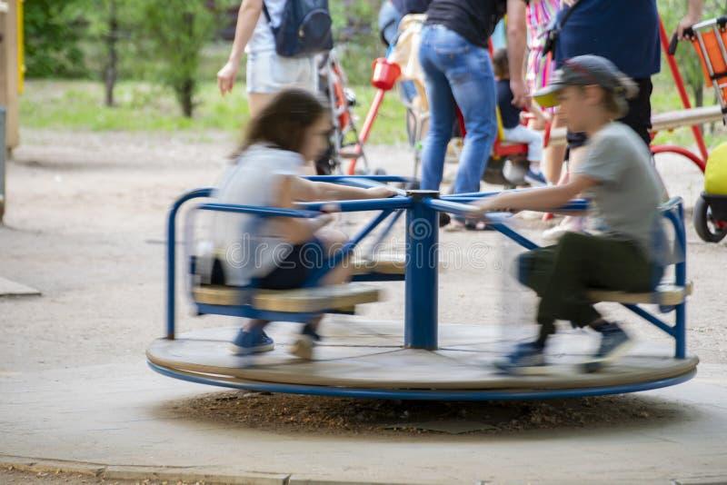 Άποψη κινήσεων του φιλικού γύρου παιδιών στο ιπποδρόμιο, χαρούμενα kidss στοκ εικόνα