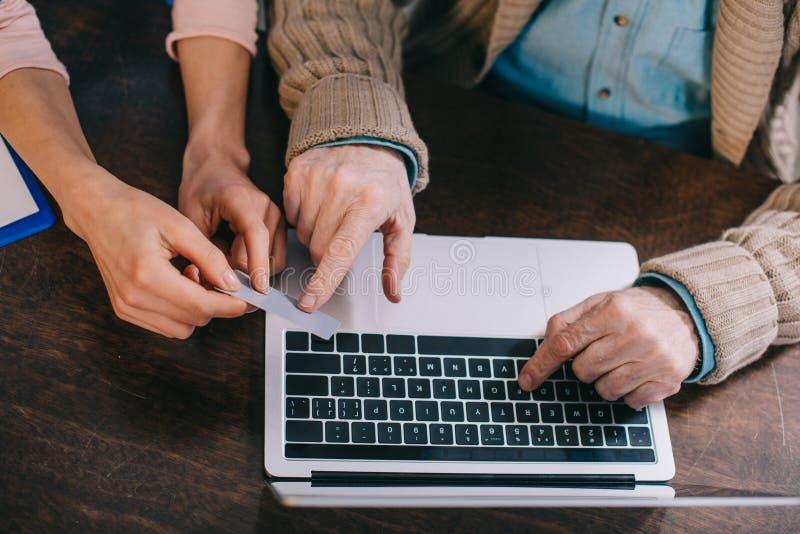 Άποψη κινηματογραφήσεων σε πρώτο πλάνο της γυναίκας που βοηθά τον ανώτερο άνδρα που χρησιμοποιεί το lap-top και την πιστωτική κάρ στοκ φωτογραφία με δικαίωμα ελεύθερης χρήσης