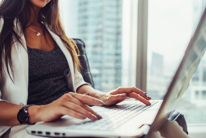 Άποψη κινηματογραφήσεων σε πρώτο πλάνο της γυναίκας που χρησιμοποιεί τη συνεδρίαση lap-top στο σύγχρονο γραφείο στοκ φωτογραφίες