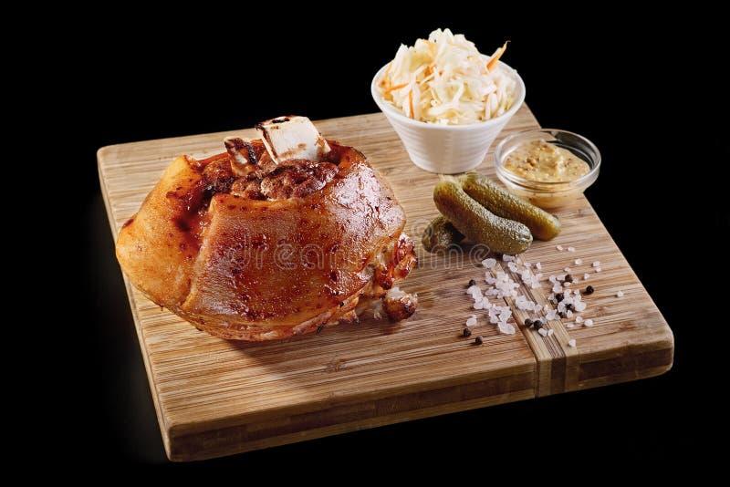 Άποψη κινηματογραφήσεων σε πρώτο πλάνο της νόστιμης ψημένης άρθρωσης χοιρινού κρέατος με τις σάλτσες στον ξύλινο πίνακα στοκ φωτογραφίες