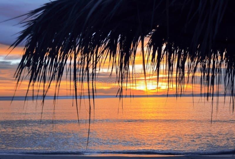 Άποψη κινηματογραφήσεων σε πρώτο πλάνο της ομπρέλας αχύρου στο ηλιοβασίλεμα, τροπική παραλία παραδείσου, κανένας άνθρωπος, καταπλ στοκ φωτογραφία