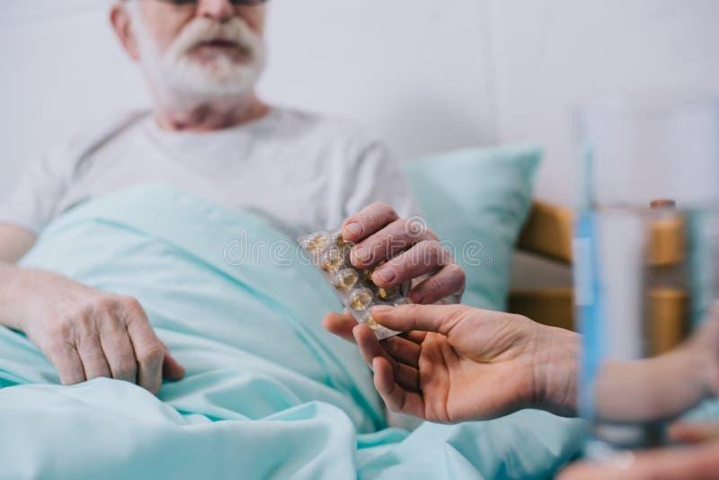 Άποψη κινηματογραφήσεων σε πρώτο πλάνο του γιατρού που δίνει τα χάπια στον ανώτερο ασθενή στοκ εικόνα