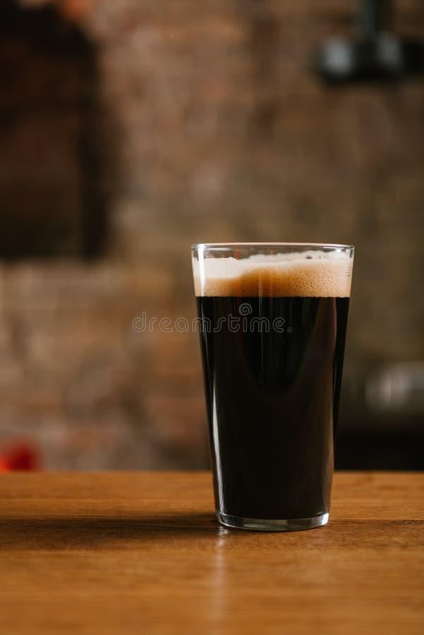 άποψη κινηματογραφήσεων σε πρώτο πλάνο του γυαλιού με την εύγευστη σκοτεινή μπύρα στον πίνακα στοκ φωτογραφία με δικαίωμα ελεύθερης χρήσης