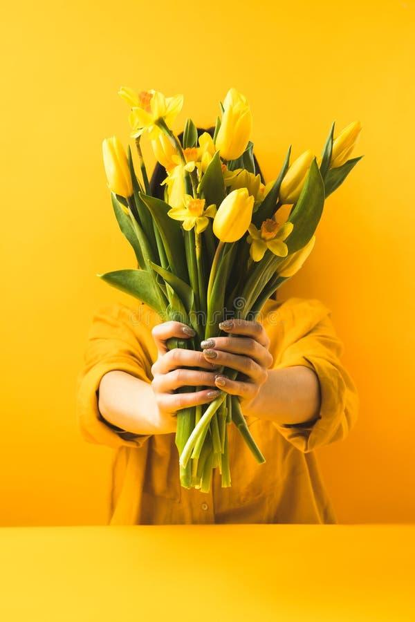 Άποψη κινηματογραφήσεων σε πρώτο πλάνο του κοριτσιού που κρατά τα όμορφα κίτρινα λουλούδια άνοιξη στοκ φωτογραφία με δικαίωμα ελεύθερης χρήσης