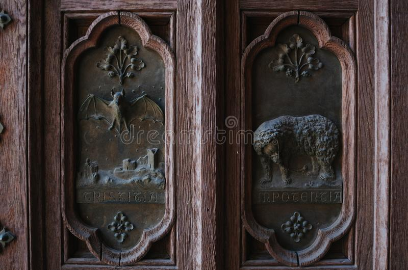 Άποψη κινηματογραφήσεων σε πρώτο πλάνο των διακοσμήσεων bas-ανακούφισης με τα ζώα στα μέρη μετάλλων της ξύλινης πόρτας της εκκλησ στοκ εικόνες