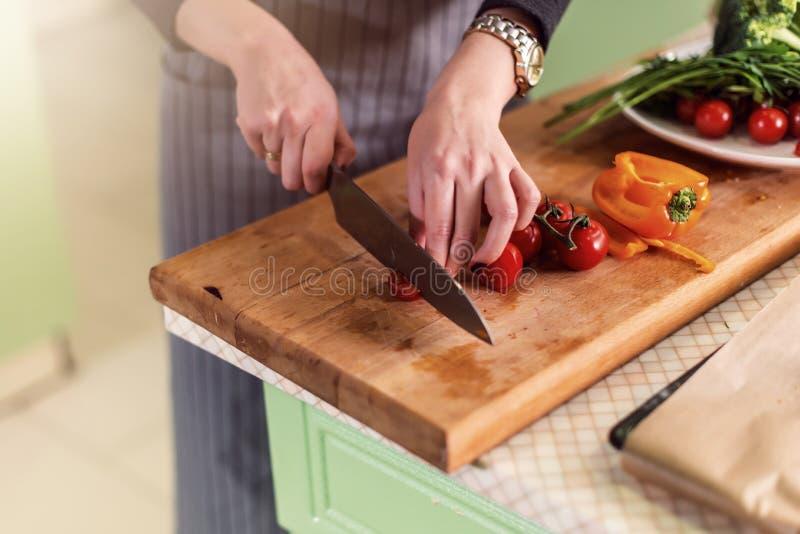 Άποψη κινηματογραφήσεων σε πρώτο πλάνο των νέων χεριών γυναικών s που κόβει τα λαχανικά εν πλω για την πίτσα σύμφωνα με το βιβλίο στοκ φωτογραφία με δικαίωμα ελεύθερης χρήσης