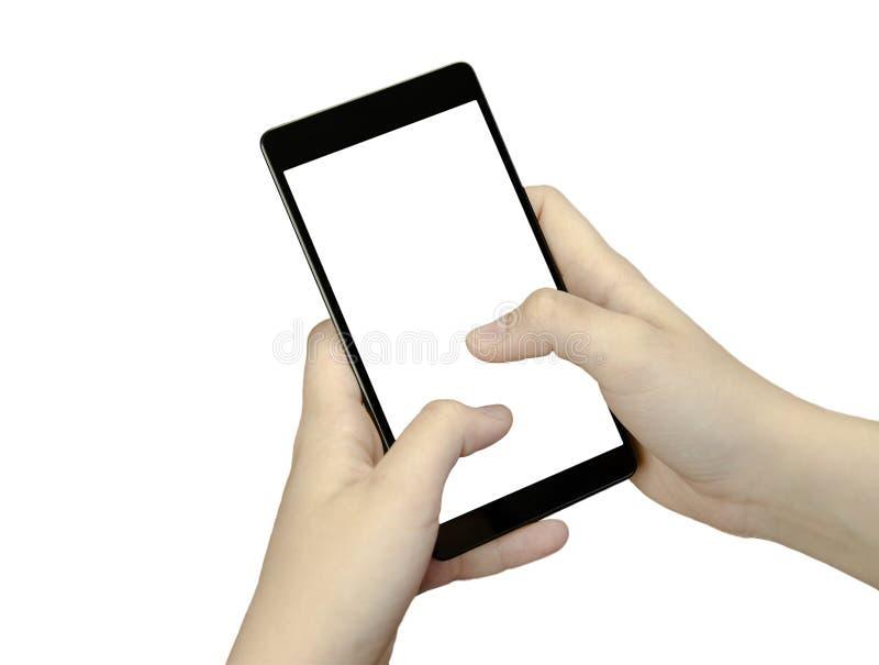 Άποψη κινηματογραφήσεων σε πρώτο πλάνο ενός χεριού με τα δάχτυλα που κρατούν ένα μαύρο τηλέφωνο κυττάρων με την άσπρη οθόνη στην  στοκ εικόνες