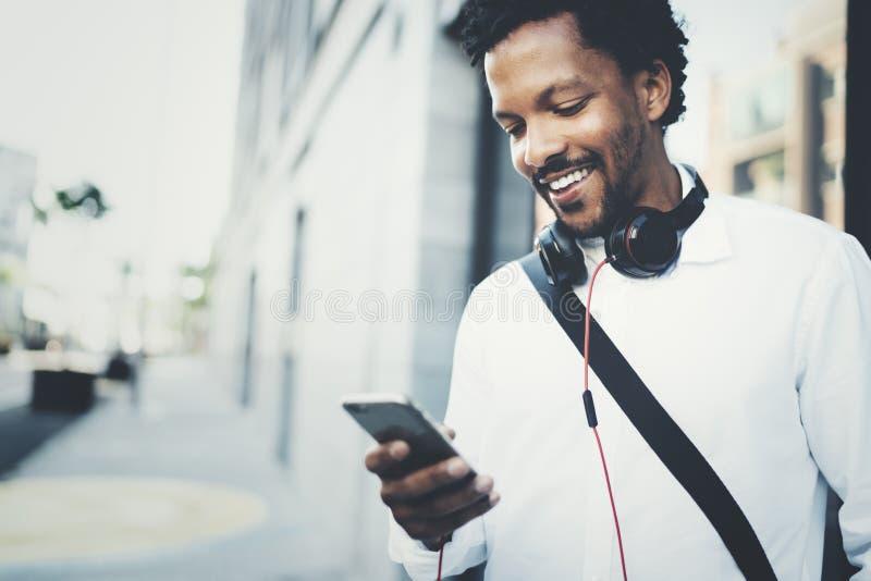 Άποψη κινηματογραφήσεων σε πρώτο πλάνο του ευτυχούς χαμογελώντας αφρικανικού ατόμου που χρησιμοποιεί το smartphone υπαίθριο Πορτρ στοκ εικόνες