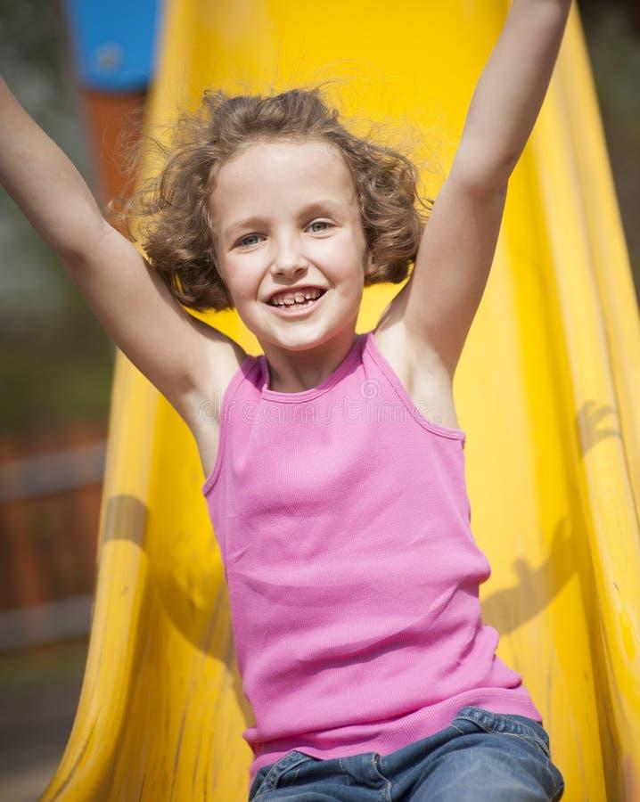 Άποψη κινηματογραφήσεων σε πρώτο πλάνο του νέου κοριτσιού στη φωτογραφική διαφάνεια στην παιδική χαρά στοκ εικόνα με δικαίωμα ελεύθερης χρήσης