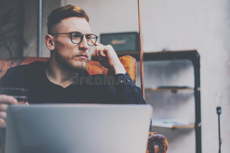 Άποψη κινηματογραφήσεων σε πρώτο πλάνο του σκεπτικού γενειοφόρου επιχειρηματία eyeglasses που λειτουργούν στη σύγχρονη σοφίτα Συν στοκ εικόνα
